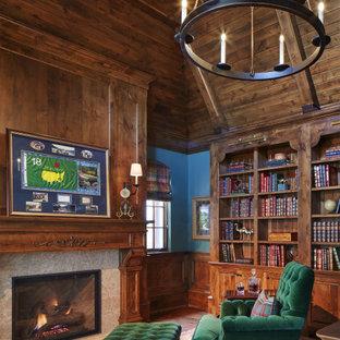 Inredning av ett mellanstort hemmabibliotek, med blå väggar, heltäckningsmatta, en standard öppen spis, en spiselkrans i sten, ett fristående skrivbord och flerfärgat golv