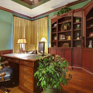 Home office - mediterranean freestanding desk dark wood floor home office idea in Orlando with green walls