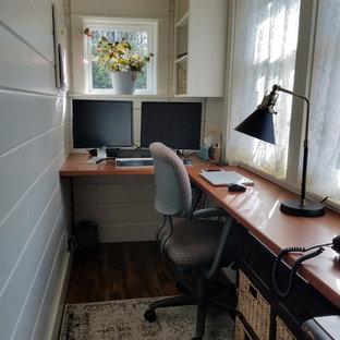 Пример оригинального дизайна: маленький кабинет в стиле кантри с белыми стенами, полом из ламината, встроенным рабочим столом, коричневым полом, сводчатым потолком и стенами из вагонки