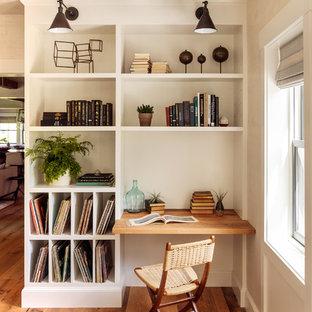 Cette photo montre un bureau nature avec un mur beige, un sol en bois brun, un bureau intégré et un sol marron.