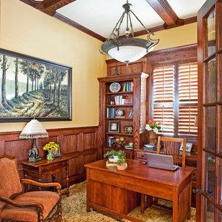 Идея дизайна: рабочее место среднего размера в классическом стиле с желтыми стенами, темным паркетным полом и отдельно стоящим рабочим столом