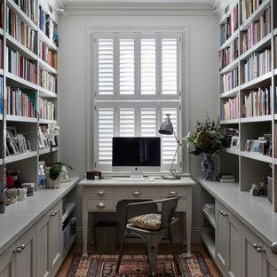ロンドンの中サイズのトランジショナルスタイルのおしゃれなホームオフィス・仕事部屋 (グレーの壁、淡色無垢フローリング、自立型机、ベージュの床、ライブラリー) の写真