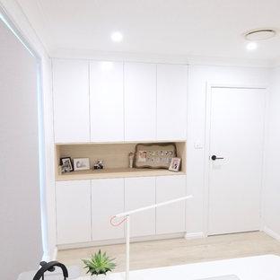 シドニーの中サイズのモダンスタイルのおしゃれな書斎 (白い壁、ラミネートの床、自立型机、ベージュの床) の写真
