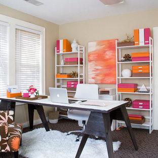 Inredning av ett eklektiskt litet hemmabibliotek, med beige väggar, heltäckningsmatta och ett fristående skrivbord