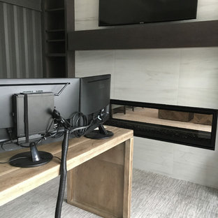 Idee per un grande ufficio moderno con pareti grigie, moquette, camino lineare Ribbon, cornice del camino piastrellata, scrivania autoportante e pavimento grigio