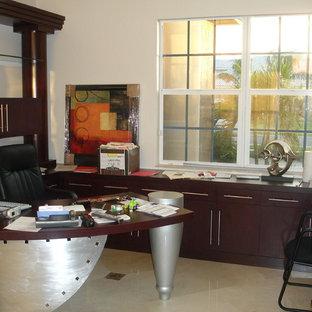 マイアミの中サイズのエクレクティックスタイルのおしゃれな書斎 (ベージュの壁、磁器タイルの床、暖炉なし、造り付け机、ベージュの床) の写真