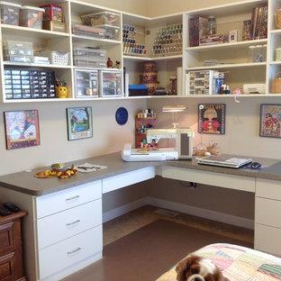 Foto på ett mellanstort funkis hobbyrum, med vita väggar och ett inbyggt skrivbord
