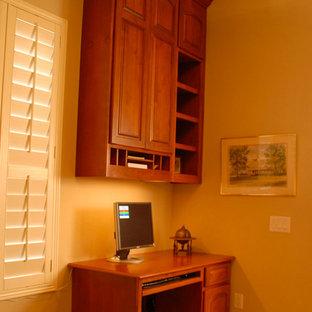 Esempio di un ufficio american style di medie dimensioni con pareti gialle, pavimento in legno massello medio, nessun camino e scrivania incassata