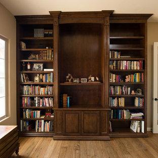 Immagine di un ufficio american style di medie dimensioni con pareti gialle, pavimento in legno massello medio, nessun camino e scrivania incassata