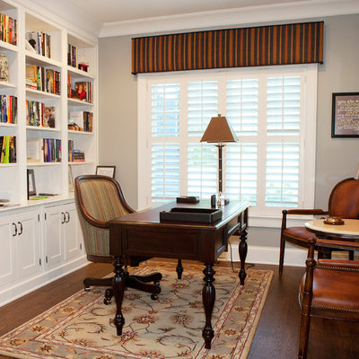 Example of a mid-sized classic freestanding desk dark wood floor and brown floor study room design in Chicago with gray walls and no fireplace
