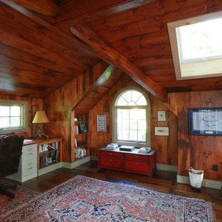Rustik inredning av ett mellanstort hemmabibliotek, med bruna väggar, mörkt trägolv, en öppen vedspis och ett inbyggt skrivbord