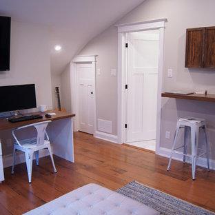 Cette photo montre un grand bureau chic avec un mur gris, un sol en bois brun, un bureau intégré et aucune cheminée.