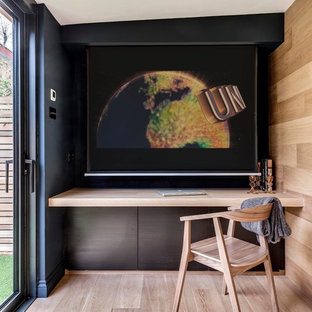 Example of a trendy built-in desk light wood floor home office design in London with beige walls
