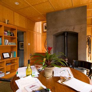 Неиссякаемый источник вдохновения для домашнего уюта: маленькое рабочее место в современном стиле с бетонным полом, печью-буржуйкой, фасадом камина из бетона и отдельно стоящим рабочим столом