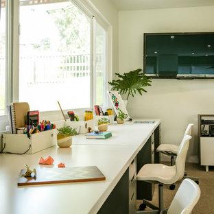 Неиссякаемый источник вдохновения для домашнего уюта: рабочее место среднего размера в стиле модернизм с белыми стенами, ковровым покрытием, стандартным камином, фасадом камина из плитки, отдельно стоящим рабочим столом и бежевым полом