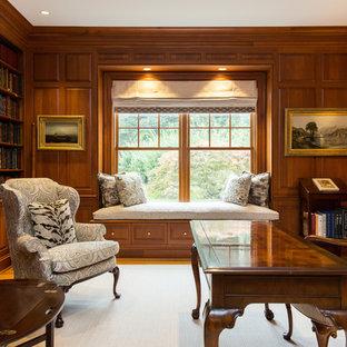 ニューヨークの中くらいのトラディショナルスタイルのおしゃれなホームオフィス・書斎 (ライブラリー、茶色い壁、濃色無垢フローリング、標準型暖炉、木材の暖炉まわり、自立型机、茶色い床) の写真