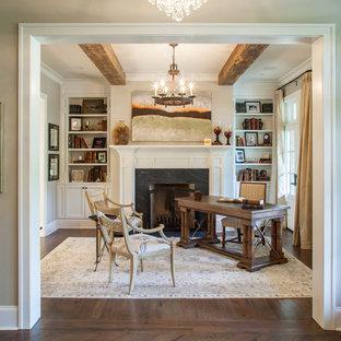 Modelo de despacho clásico, de tamaño medio, con paredes beige, suelo de madera oscura, chimenea tradicional, marco de chimenea de piedra y escritorio independiente