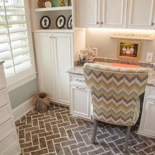 Неиссякаемый источник вдохновения для домашнего уюта: маленькое рабочее место в классическом стиле с кирпичным полом, встроенным рабочим столом, синими стенами и коричневым полом без камина