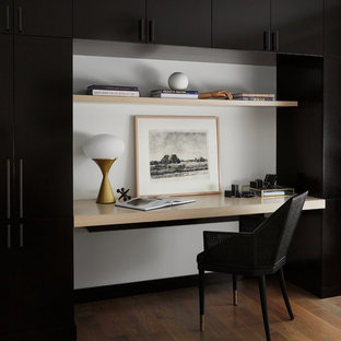 Mid-sized trendy built-in desk medium tone wood floor and brown floor study room photo in Chicago with white walls and no fireplace