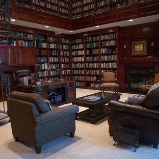Idee per un ampio studio vittoriano con libreria, pareti marroni, moquette, camino classico, cornice del camino piastrellata, scrivania autoportante e pavimento grigio