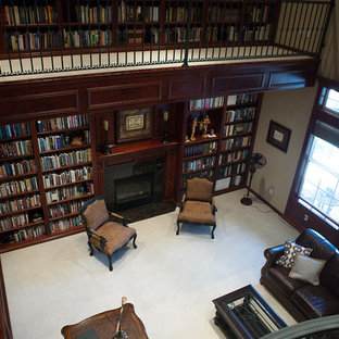 Expansive victorian home office in Other with a library, brown walls, carpet, a standard fireplace, a tile fireplace surround, a freestanding desk and grey floor.