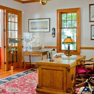 Immagine di uno studio tropicale con pareti grigie, pavimento in legno massello medio e scrivania autoportante
