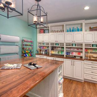 Неиссякаемый источник вдохновения для домашнего уюта: большой кабинет в классическом стиле с синими стенами, местом для рукоделия и паркетным полом среднего тона