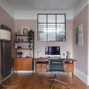 Mittelgroßes Klassisches Arbeitszimmer mit rosa Wandfarbe, braunem Holzboden, freistehendem Schreibtisch und braunem Boden in London