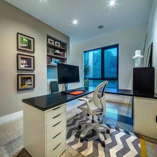 タンパの中くらいのモダンスタイルのおしゃれなホームオフィス・書斎 (グレーの壁、コンクリートの床、暖炉なし、自立型机) の写真