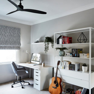 This is an example of a mid-sized contemporary study room in Sydney with grey walls, carpet, a freestanding desk and grey floor.