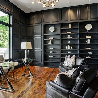 Idéer för att renovera ett stort vintage hemmabibliotek, med svarta väggar, mörkt trägolv, ett fristående skrivbord och brunt golv