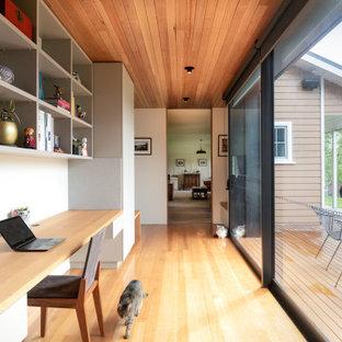 Modernes Arbeitszimmer mit weißer Wandfarbe, hellem Holzboden, Einbau-Schreibtisch, beigem Boden und Holzdecke in Hobart