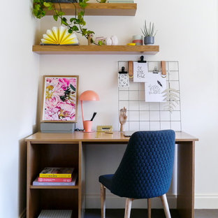 This is an example of a contemporary home office in Melbourne with white walls, carpet, a freestanding desk and blue floor.