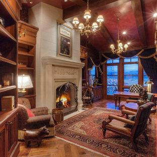 ソルトレイクシティの巨大なトラディショナルスタイルのおしゃれな書斎 (無垢フローリング、標準型暖炉、漆喰の暖炉まわり、自立型机) の写真