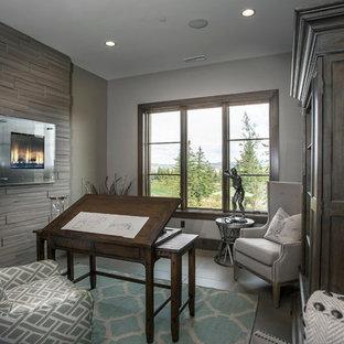 ソルトレイクシティの中サイズのラスティックスタイルのおしゃれなアトリエ・スタジオ (グレーの壁、セラミックタイルの床、標準型暖炉、石材の暖炉まわり、自立型机) の写真