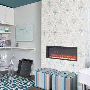 トロントの小さいトランジショナルスタイルのおしゃれなホームオフィス・仕事部屋 (白い壁、ラミネートの床、標準型暖炉、金属の暖炉まわり、茶色い床) の写真