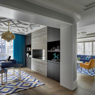 Immagine di uno studio classico con pareti grigie, pavimento in legno massello medio, camino bifacciale, scrivania autoportante e pavimento marrone