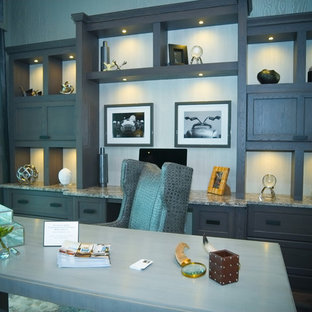 マイアミの巨大なトランジショナルスタイルのおしゃれな書斎 (グレーの壁、標準型暖炉、石材の暖炉まわり、自立型机) の写真