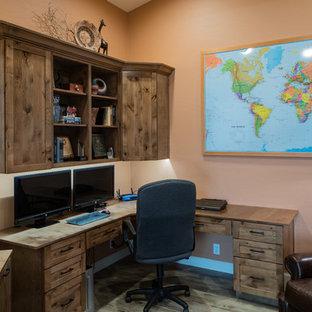 Immagine di uno studio stile rurale di medie dimensioni con libreria, pareti arancioni, pavimento in gres porcellanato, nessun camino, scrivania incassata e pavimento beige