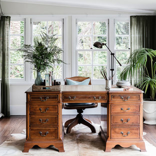 Large traditional study room in Sydney with beige walls, dark hardwood floors and a freestanding desk.