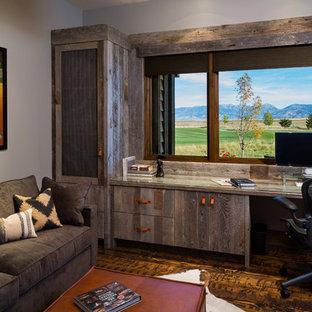 Idéer för stora rustika hemmabibliotek, med beige väggar, mellanmörkt trägolv, ett inbyggt skrivbord och brunt golv