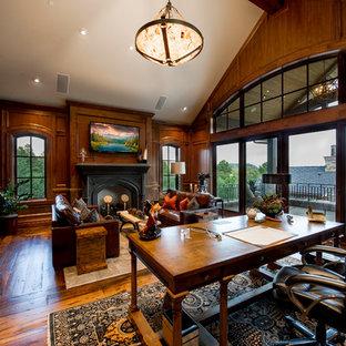 Inspiration pour un grand bureau chalet avec un sol en bois brun, un bureau indépendant, un mur marron, une cheminée standard, un manteau de cheminée en bois et un sol marron.