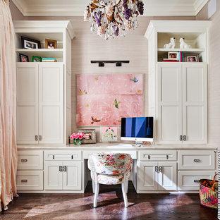 На фото: большое рабочее место в классическом стиле с розовыми стенами, темным паркетным полом, встроенным рабочим столом и коричневым полом без камина с