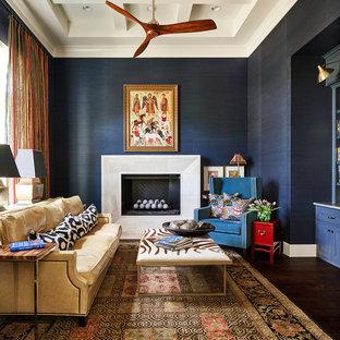Großes Klassisches Arbeitszimmer mit Arbeitsplatz, blauer Wandfarbe, dunklem Holzboden, Kamin, Kaminsims aus Stein und Einbau-Schreibtisch in Austin