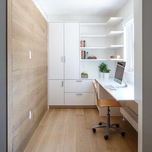 Diseño de despacho moderno, de tamaño medio, con paredes blancas, suelo de madera clara, escritorio empotrado y suelo beige