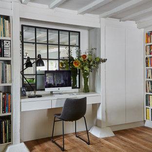 Cette image montre un bureau traditionnel avec un mur blanc, un sol en bois brun, un bureau intégré, un sol marron et un plafond en poutres apparentes.