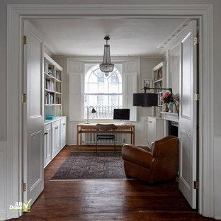 Immagine di uno studio minimal di medie dimensioni con pareti bianche, pavimento in legno massello medio, camino classico, cornice del camino in pietra, scrivania autoportante e pavimento marrone