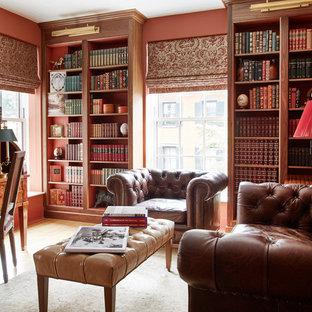 Immagine di uno studio tradizionale con libreria, pareti rosse, pavimento in legno massello medio, nessun camino e scrivania autoportante