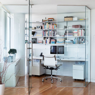 Example of a trendy built-in desk medium tone wood floor and brown floor home office design in New York with white walls