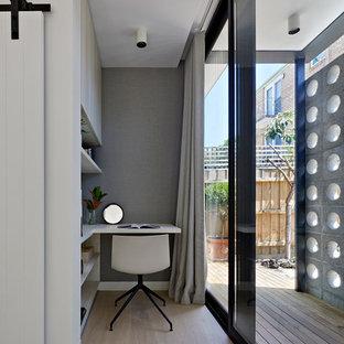 メルボルンのミッドセンチュリースタイルのおしゃれな書斎 (グレーの壁、淡色無垢フローリング、暖炉なし、造り付け机、ベージュの床) の写真
